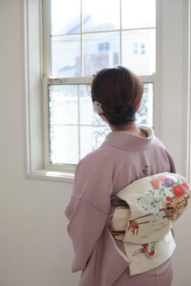 窓を見上げる着物姿の女性