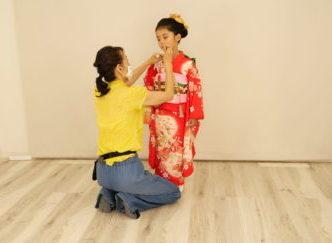 赤い着物の少女と着付け師