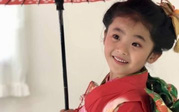 傘をさす赤い着物の女児